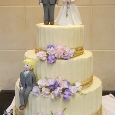 Buttercream textured wedding cake, sugar sweet peas & handmade  bride, groom and family characters