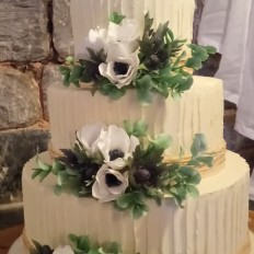 Buttercream textured wedding cake with sugar anemones, sea holly, and eucalyptus