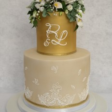 White sugar flowers, piped monogram & gold airbrushed wedding cake