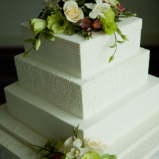 Brush embroidered royal iced wedding cake with sugar flowers